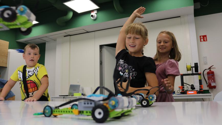 Obrazek przedstawia dziewczynkę dającą znak startu wyścigów modeli Lego