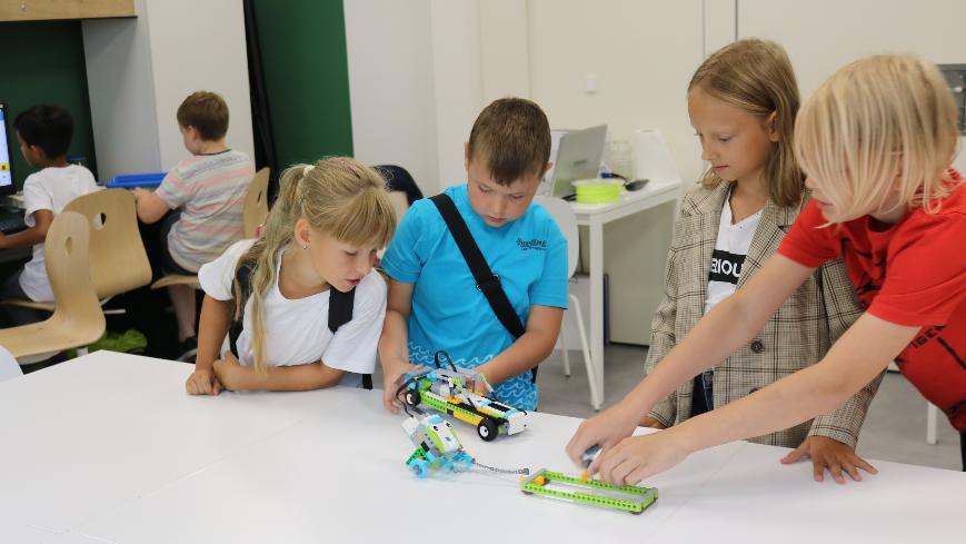 Zdjęcie przedstawia grupę dzieci prezentującą swoje modele z klocków LEGO