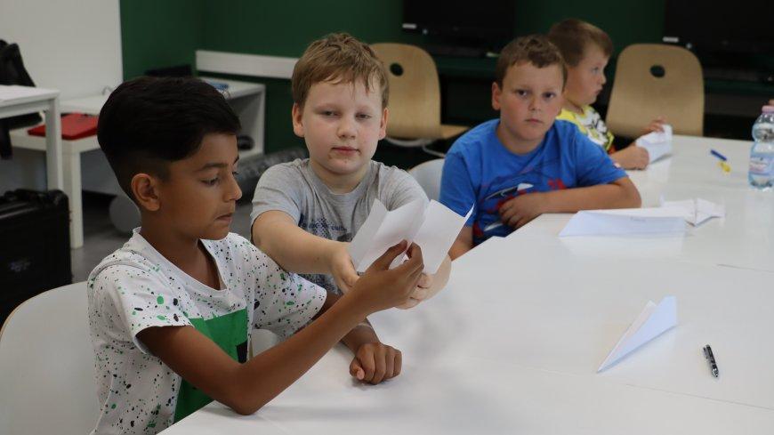 dzieci robiące samoloty z papieru