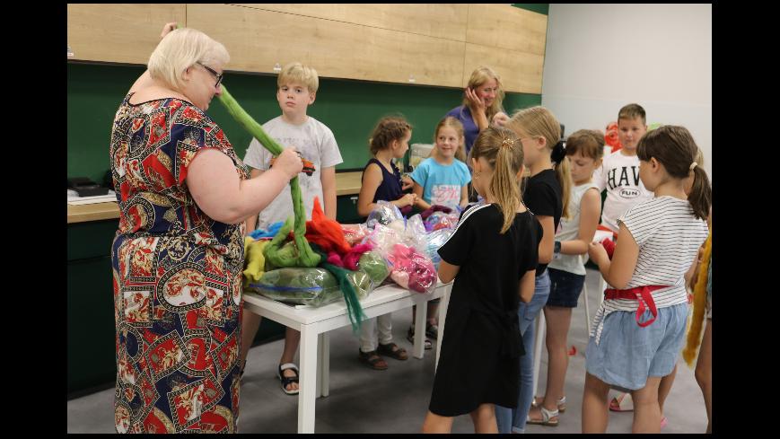 Zdjęcie przedstawia grupę dzieci wybierającą materiały do prac ręcznych