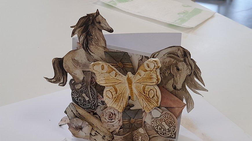 obrazek przedstawia kartkę wykonaną ręcznie na zajęciach rękodzieła. Kartka przedstawia parę koników oraz motylek wykonany z masy plastycznej